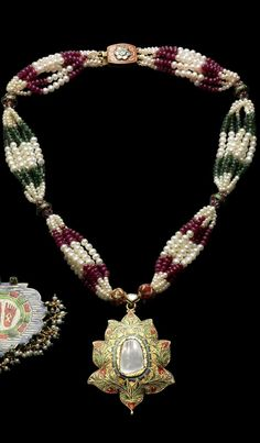 An Indian diamond-set enamelled gold Pendant   the pendant in the form of a lotus, set with a large central flat-cut diamond, the gold ground with polychrome enamel floral decoration, verso with enamelled floral decoration, on a seven-string of seed pearls, ruby and emerald beads with five diamond-set enamelled gold fittings and clasp