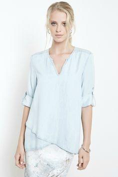 Chambray top with an asymmetric wrap hem, 3/4 rolled sleeves, and a split neck. Made in the USA. 100% Tencel. Machine wash. Fit Guide: XS: 2 Small: 4-6 Medium: 8-10 Large: 12-14 X-Large: 16