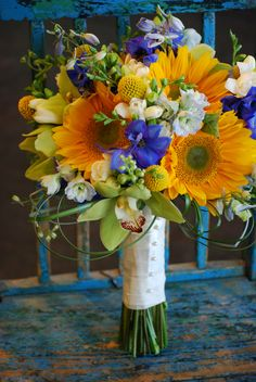 yellow gerbers with purple delphinium and white. ? orchid?