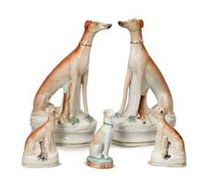 FOUR STAFFORDSHIRE MODELS OF SEATED HOUNDS WITH RABBITS,  20TH CENTURY