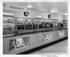 Displayed on shelving units are bottles of tonics, elixirs and powders for varying ailments are visible throughout the department. Also, featured are small displays for the latest in diabetic equipment. The Pharmacy is decorated for the Christmas holidays; wreaths are affixed to the upper perimeter of the department.