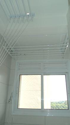 (Varal de teto, varal de parede) À frente, varal tradicional de parede de 0,67 X 1,00m com 7 varetas. À esquerda, varal individual de teto de 0,42 X 1,50m com 6 varetas. Ambos em alumínio com pintura eletrostática branca. Por que um varal de teto e um varal de parede no mesmo ambiente? Porque onde está o varal tradicional de parede, repare, tem um rebaixo de gesso. No gesso não podemos instalar varal.