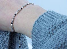 #Zierliches #Armband in Schwarz mit kleinen 2,5 mm Kügelchen aus 925 Silber. Für einen trendigen Look einzeln oder mit mehreren #Armbändern kombinierbar.   Das Armband besitzt einen #Knotenverschluss für verstellbare Länge.  Ein einzigartiges #handgemachtes #Schmuckstück für dich. Designed by Schoschon.