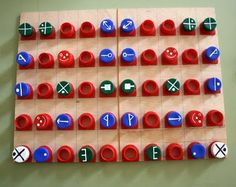 Symmetry game made with milk carton screw caps and a plywood board