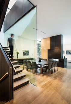 In this modern house, a large square dining area with a table big enough to seat nine people sits between the staircase and a fireplace. #DiningRoom #SquareDiningTable