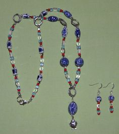 "This 26-1/2"" necklace is made with blue and white porcelain beads, light sapphire glass cubes, clear oval glass, red Czech glass beads and pewter rings. Hanging from the center pendant bead is a silver tone fish. The necklace is closed with a lobster claw clasp.The matching earrings measure 2"" in length, made with some of the same beads as the necklace and on flat silver plated ear wires. - SOLD"