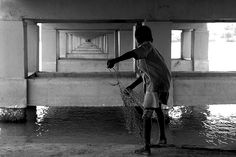 Photo of the Day: Fishing Under the Bridge in India |  A young boy casts his fishing net into the water beneath a bridge in Chennai, #India on May 12, 2013. (Aschevogel/Flickr)