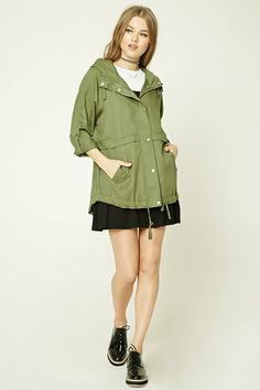 A lightweight woven utility jacket featuring a drawstring hood and hem, a zipper and button front, slanted front pockets, long sleeves with button cuffs, and high-polish details.