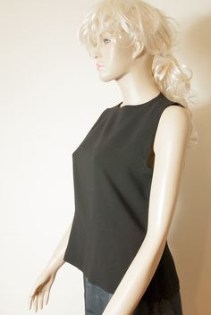 Max Mara - A black sleeveless shirt with round neck. Down in the form of fashionable baskinki slightly marked. On the back of the clasp on one button on the back of the neck with a crack in the shape of a teardrop
