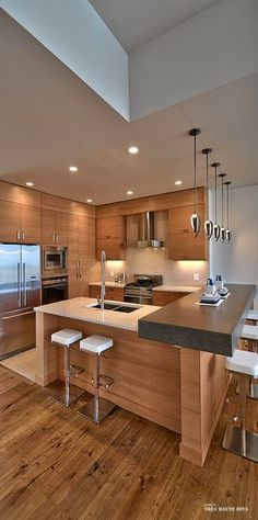 L shaped seating around kitchen. Sink on lower counter, range facing main (higher) seating area