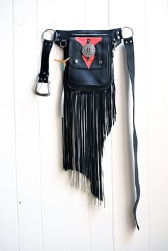 Fringe Bag/Biker Bag  Revivall Clothing's convertible leather Hip Bag can be worn two ways- as a belt or across your shoulder as a crossbody bag. They are perfect for traveling, festivals, a night out dancing, or just casually around town. There are 3 large pockets- an outer patch pocket with snap closure, a larger zipper pocket behind it, and 2 slip pockets in the very back. The zipper pocket will fit a mini iPad. I like to use the slip pocket to put receipts, papers, or things you nee...