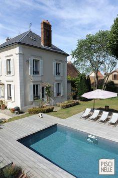 Piscine traditionnelle dans un pavillon de région parisienne. La piscine est au pied d'un bel hôtel particulier comme un miroir reflétant fenêtres et cheminées.