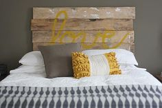 Gorgeous diy rustic wood love headboard with brown gray walls paint color, DIY Love headboard, Ikea gray wool throw blanket, taupe pillow and bright yellow ruffled pillow.