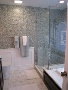 Glass enclosed shower over tub ledge. I want this. Wainscoting higher on the wall and cork on the floors.