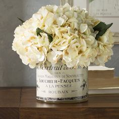 Faux hydrangea blooms in a french label decoupage glass pot perfect for vanity table.