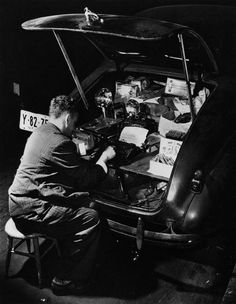 Weegee(arthur Fellig)/internatio / Getty Images Contributor Hungarian-born photographer Arthur Fellig, aka Weegee, sits on a stool, typing on a typewriter in the trunk of his Chevrolet while smoking a cigar in 1942.