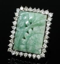 A modern silvery coloured metal mounted nephrite and diamond set dress ring, the oblong pale green p