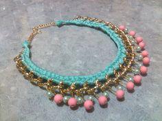 Collar de cadena en oro, con tejido en color verde, y perlas colgantes de colores verde y rosa.