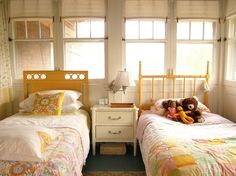 LOVE the bright yellow headboard. And the quilt/blanket rack as clothing storage. Cute room for little girls!