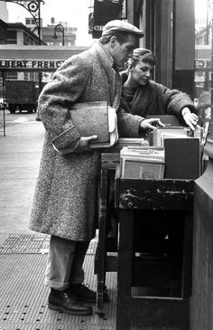 Paul Newman and Joanne Woodward browsing books on the street, 1950s.