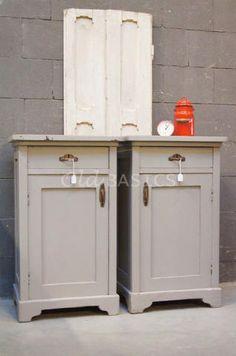 Set landelijke nachtkastjes in een grijze kleur. Op de lades en deurtjes zitten mooie koperen grepen. De voet van de kastjes hebben een sierlijke golving €259 | Old Basics