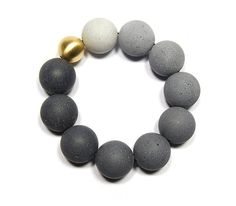 From a new line of concrete jewelry by Vancouver-based jewelry studioKonzuk. The culmination of a three-year experiment with the material, the Orbis line features tinted concrete combined with 18K gold.