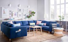 Lys stue med en stor U-formet sofa til ni personer, dekket med mørkt blått tekstil. Kombinert med et bord i askefiner og et rundt brettbord i rotting med oppbevaring.