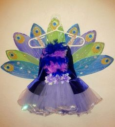 A DIY peacock costume tutorial. Using Dollar Store butterfly wings, paint, glitter, ribbon, and felt!