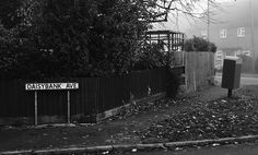 Street Names Rothwell Northamptonshire UK ~aka Dennis Thorpe  For no other reason than I liked this image and wondered what it would look like in black and white. It was a gloomy foggy day too so that didnt really add to the contrast that I was looking for. The picture makes you want to know what is around the corner, whilst the name conjures up an image of a flower strewn avenue, which it isnt! Took three shots trying to expose for contrast but the fog seemed to dampen that down.