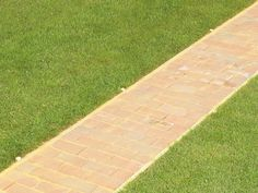 How to Lay a Brick Pathway: Drive the pegs below the grass to start and leave them in place. From DIYnetwork.com
