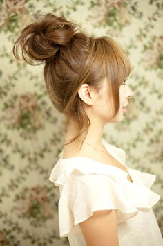 This updo is adorable, super feminine and really easy to do even on curly hair! Make a high ponytail leaving the front hair free. Backcomb the outside part of the ponytail. Pin the rest of the hair loosely over top to create the bun. I pin my side curls down behind my ears, too.