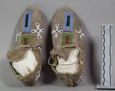Moccasins, Cheyenne. ДА1.  Col. Joseph T. Clarke, 1926.  George Levi and Max Bear of the Cheyenne delegation from the Cheyenne and Arapaho Tribes of Oklahoma  identify these as a little boy's moccasins, during the Recovering Voices Community Research Visit November 3-6, 2015. The horseshoe represents a horse, this was a common design in 1860s and 1870s. It is possbily made of buffalo hide, and it has a morningstar bead design. These are old school style moccasins. NMNH.