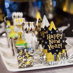 Fill a clear cup with confetti and add a blow-out and popper. Set the confetti-bombs next to a party hat on the same tray, and make the midnight revelry a blast!   Shop Black & Gold NYE Wearables