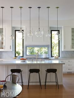 A lineup of glass pendants in different shapes and sizes lends subtle interest to the streamlined kitchen. Architectural, interior, and landscape design: SBP Homes. Cedar Shingle Siding, Riverside House, Floating Staircase, New England Homes, Interior Decorating, Interior Design, House And Home Magazine, White Walls, Decoration