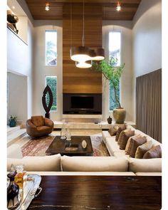 Living com pé direito duplo. A madeira reveste a lareira o painel de TV e se estende pelo teto. Andreza de Lucca