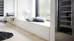 De store skuffer danner en bred bænk, hvor man kan slænge sig og nyde udsigten. Bænken begynder i kontoret og fortsætter ind i soveværelset, så der dannes en visuel sammenhæng mellem de to rum. Se mere fra boligen på www.jke-design.dk.