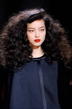 """With the beachy waves we've been seeing on the catwalks for many seasons now, this billowing style at Marc by Marc Jacobs set a new standard for curly hair. The voluminous ringlets paired with a mini pompadour looked fun and playful, and admittedly """"a little crazy"""". Cited as a 1940s-era uptown girl as the inspiration."""