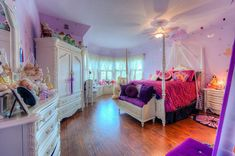 Beautiful girls bedroom with white furniture and bright purple decor