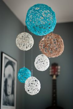 Yarn Ball Mobile - Make a solution of glue and water. Wet the yarn with mixture and wrap around an inflated balloon, let dry overnight. If you use water balloons filled with air and wrapped with string they can be fitted over Christmas lights to decorate your patio/porch year round.