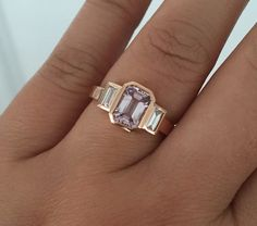 Handmade 3 stone 14K rose gold bezel ring featuring a natural emerald cut fancy pink sapphire measuring 7.2 x 5.2 mm and weighing 1.23 ct. Center