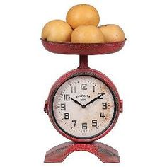 Cool vintage-inspired design will be yours with the 2-Side Scale Shaped Clock - Red. This unique piece of home decor harkens back to the good old days with its fun retro scale concept that doubles as a functional clock. Featuring a weathered metal exterior, a numeral clock face with faux distressing and a recessed bowl on top for storing decorative items or essentials.