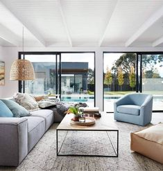 soft blue armchair in living room with grey sectional sofa from globewest