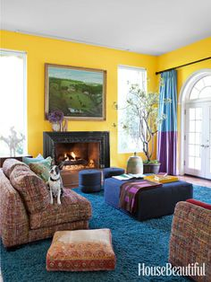 A bright yellow living room made brighter with pops of more bold colors.