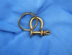 "Solid Brass Bow Shackle & Splitring. These solid brass shackles are great for ropework projects, keychains and other uses where corrosion isn't an option! Shackle weighs 0.7 ounces. Includes 1.25"" dia. brass split ringShackle measures 1.25"" tall by 7/8"" wide at widest outside part by  1/2"" opening width at pin."