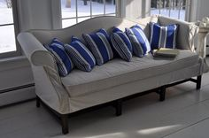 Slip Covered Camel Back Sofa With Blue Striped Pillows.