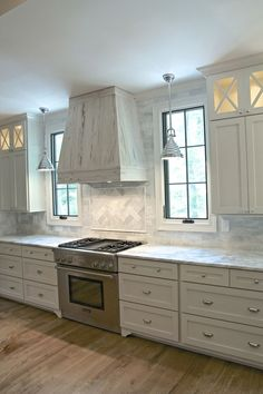 White Shaker Cabinets, Full Overlay Cabinets, Bin Pulls, Polished Nickel, Thermador Range, Pecky Cypress, Windows Flanking Range, Lighted Cabinets, Marble Countertops, White Kitchen, White Oak Floors, Timeless Kitchen, Timeless Design, Herringbone Backsplash, Tile to the Ceiling, Black Windows