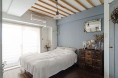 夫のベッドルーム。ブルーグレーの塗装、天井の梁、ドアの塗装はすべてDIY。南仏のアトリエをイメージした。