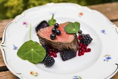 Grilled beef filet with forest berries, potatoes, blackcurrant butter, chanterelles and pearl onions.