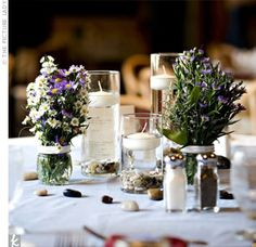 Aleta's godparents own a flower shop and provided blooms for the centerpieces. Eryngium, wax flowers, asters, limonium, and baby's breath were placed in small jars. White river stones and floating candles in different sized hurricane vases completed the l...