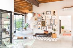 large gallery wall with bench below it; mint chairs around table
